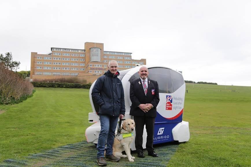 Blind veterans standing next to an Aurrigo autonomous pod